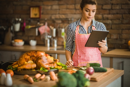 woman looking at a tablet with a cooked turkey in the foregound